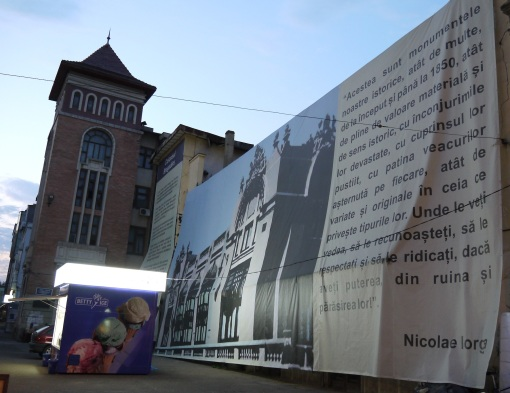 Protective cover over a building in renovation, with quote from Nicolae Iorga, Romanian historian