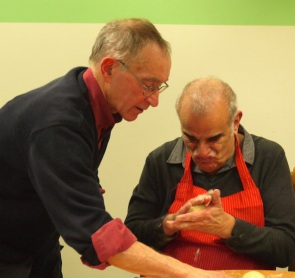Keiran shapes a roll while volunteer supporter Mick outs one made into the baking tin