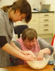 Marie gets her hands in the mix while her support worker steadies the bowl