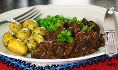 Boeuf Bourguignon on the plate with parslied potatoes and peas