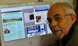 The author at a computer with some of his writing on the screen