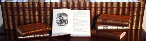 Library of the complete works of Charles Dickens, with a volume of Christmas Stories open at 'A Christmas Carol'