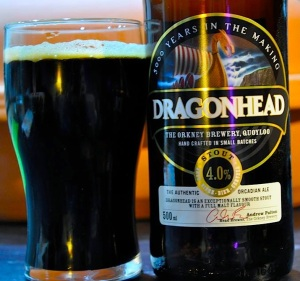 Glass of Dragonhead stout with the bottle