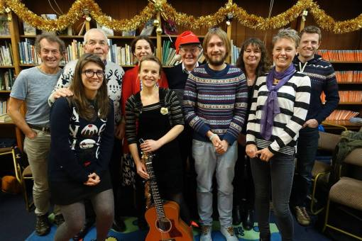 Picture of all the 'performers' lined up after their performances in the Ilkley library, with book-fillwed shelves behind.