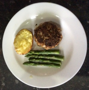 'Romanian hamburger' with baked potato and asparagus on a plate, before 'saucing'
