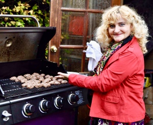 Petronela at the barbecue with 'mici' cooking