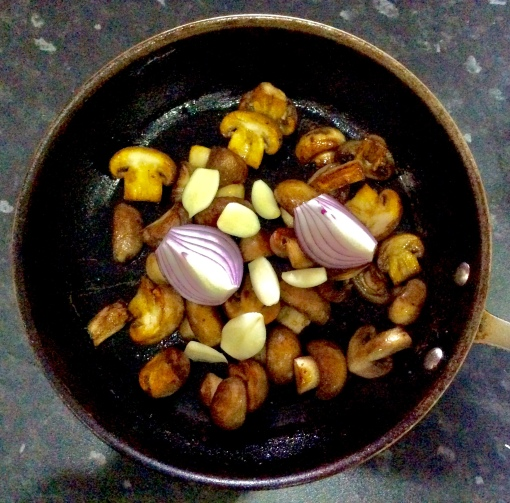 Unchopped onion and uncrushed garlic on the cooked mushrooms to show the proportions I used