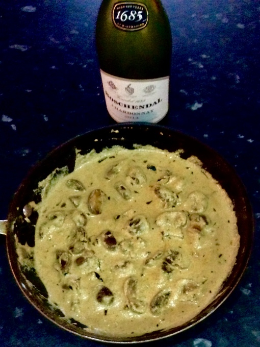 The finished dish in the pan, with a 'good' Chardonnay