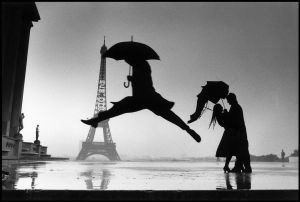 Silhouettes of couple kissing and figure of person with umbrella jumping, with Eiffel Tower in the backgrounc