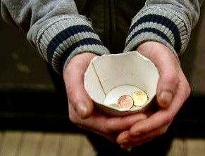 Photo of cup with a few coins in the hands of a beggar