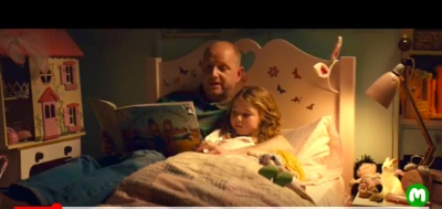 Start of Macmillan tv advertisement showing a dad reading a bedtime story to his small daughter
