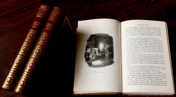 "Photo of the book ""Christmas books"", open in Chapter 1, with the two volumes of 'Christmas Stories'"